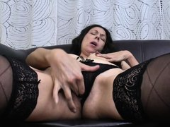 Delana lays on her black leather couch while she is wearing her sexy black lingerie. She rubs her ti